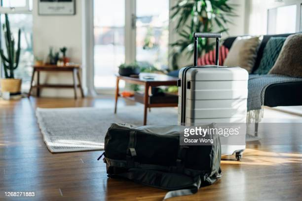 still-life of suitcase and carry bag, on the floor of cool holiday apartment - suitcase stock pictures, royalty-free photos & images