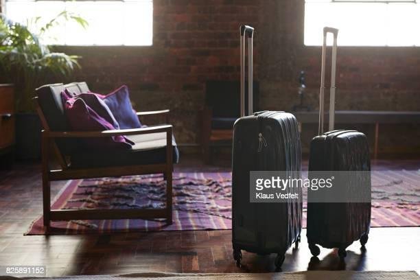 still-life of suitcases and shoulder bag, on the floor of cool holiday apartment - bolsa preta - fotografias e filmes do acervo