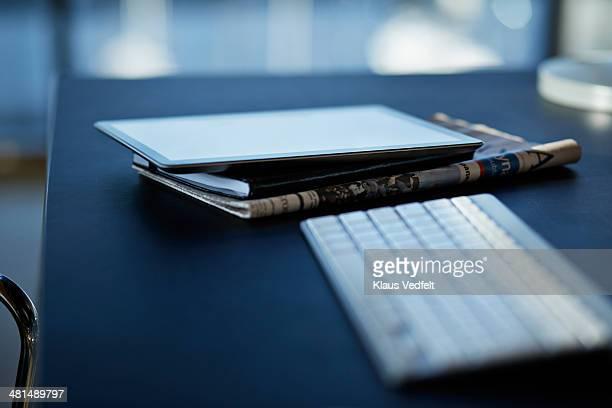 Still-life of tablet, notebook & newspaper