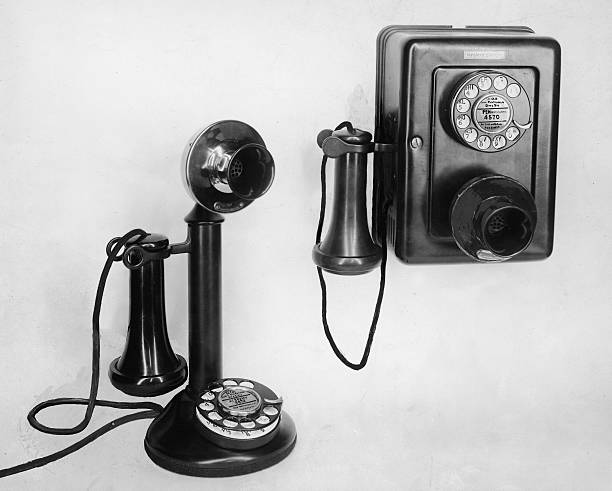 Still-life of two old-fashioned telephones, a candlestick...