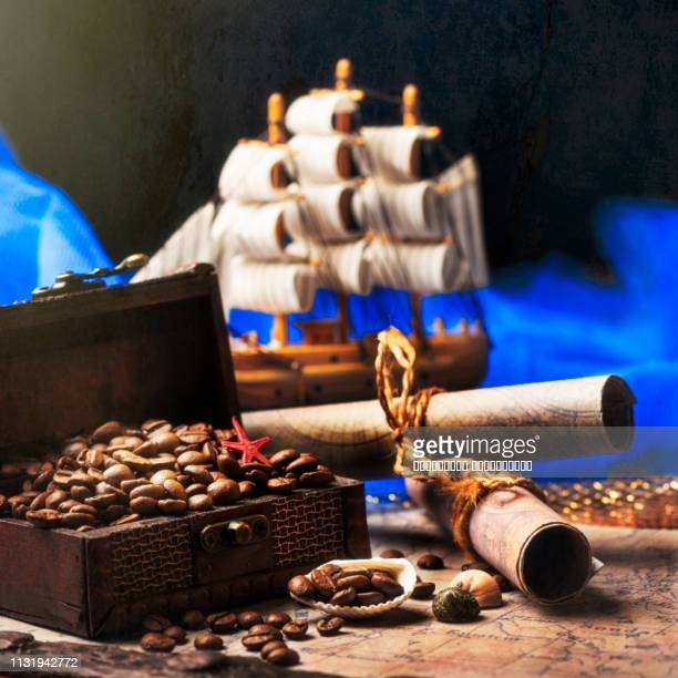 still-life. old wooden chest and black golden coffee beans. seashell and navigation map. - ancient stock pictures, royalty-free photos & images