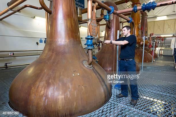 Stillsman inspecting copper spirit stills in the Stillshouse at Talisker Whisky Distillery making single malt whisky in Carbost on Isle of Skye...