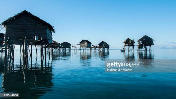 stilt houses by sea against clear sky - island of borneo stock pictures, royalty-free photos & images
