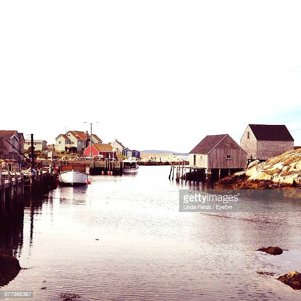 Stilt Houses By Water Against Clear Sky At Peggys Cove