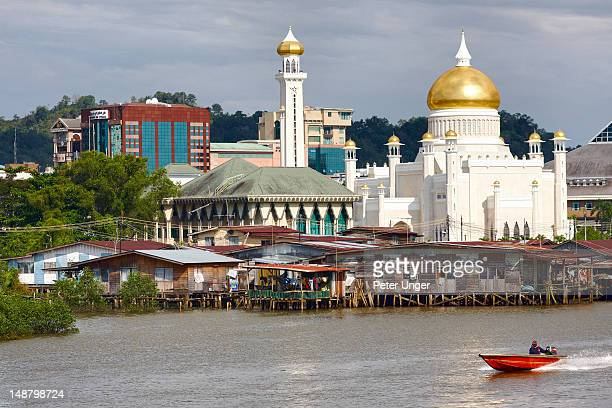 Stilt houses on Sungai Kerdayan river with Omar Ali Saifuddien Mosque in background and water taxi passing by.