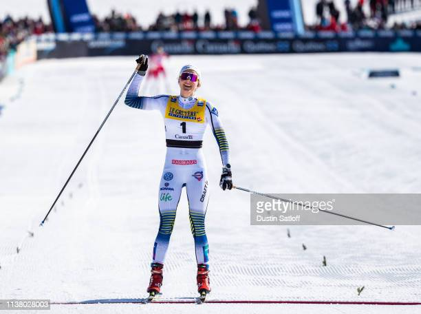 Stina Nilsson of Sweden celebrates as she crosses the finish line in first place in the Women's 10km freestyle pursuit during the FIS Cross Country...
