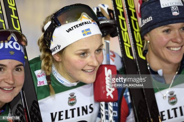 Stina Nilsson of Sweden poses with second placed Sadie Bjornsen of the US and third placed Yulia Belorukova of Russia after the Ladies' Sprint...