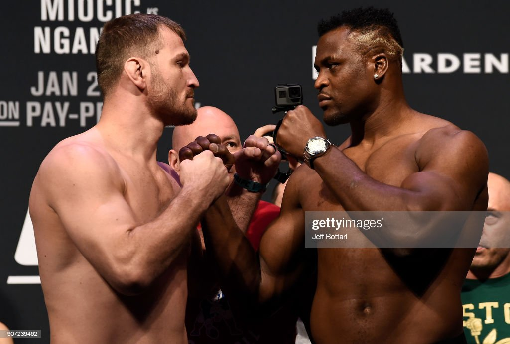 Stipe Miocic and Francis Ngannou of Cameroon face off during the UFC 220 weigh-in at TD Garden on January 19, 2018 in Boston, Massachusetts.