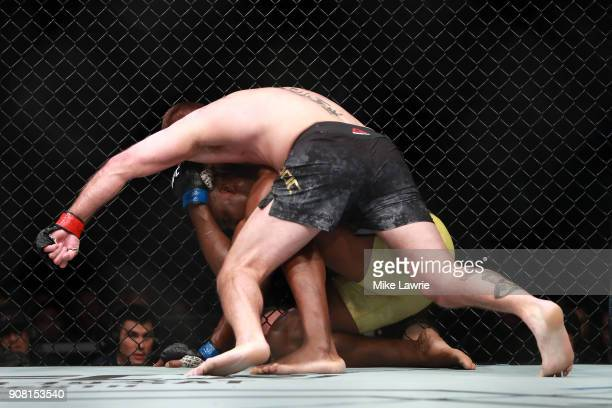 Stipe Miocic grapples with Francis Ngannou in their Heavyweight Championship fight during UFC 220 at TD Garden on January 20 2018 in Boston...