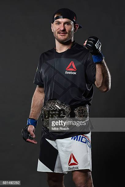 Stipe Miocic poses with his new UFC heavyweight championship belt backstage during the UFC 198 event at Arena da Baixada stadium on May 14, 2016 in...