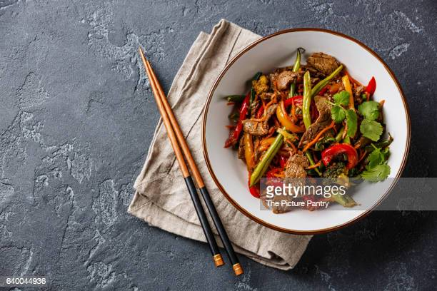Stir fry beef with vegetables in bowl on dark stone background
