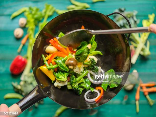 stir frying and sauteing a variety of fresh colorful market vegetables in a hot steaming wok with vegetables on on a turquoise colored wood table background below the wok. - vegetable stock pictures, royalty-free photos & images