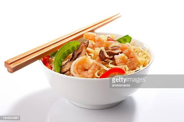 Stir-fried Asian noodles with prawns and chopsticks.