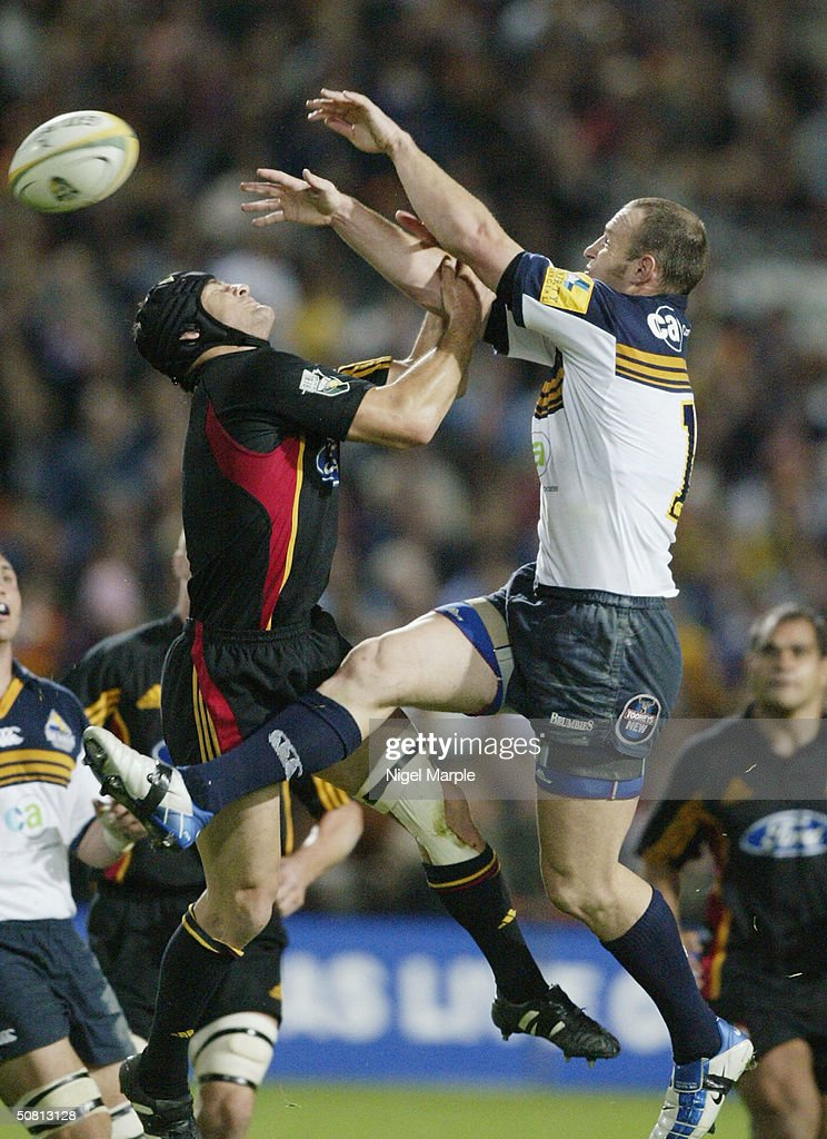 Stirling Mortlock #13 of the Brumbies challenges Marty Holah #7 for the kick off ball during the Super 12 game between the Chiefs and Brumbies at Waikato Stadium in Hamilton, New Zealand on May 8, 2004. The Chiefs scored a point by finishing within 8 points of the Brumbies to go through. The Brumbies won the match 15-12.