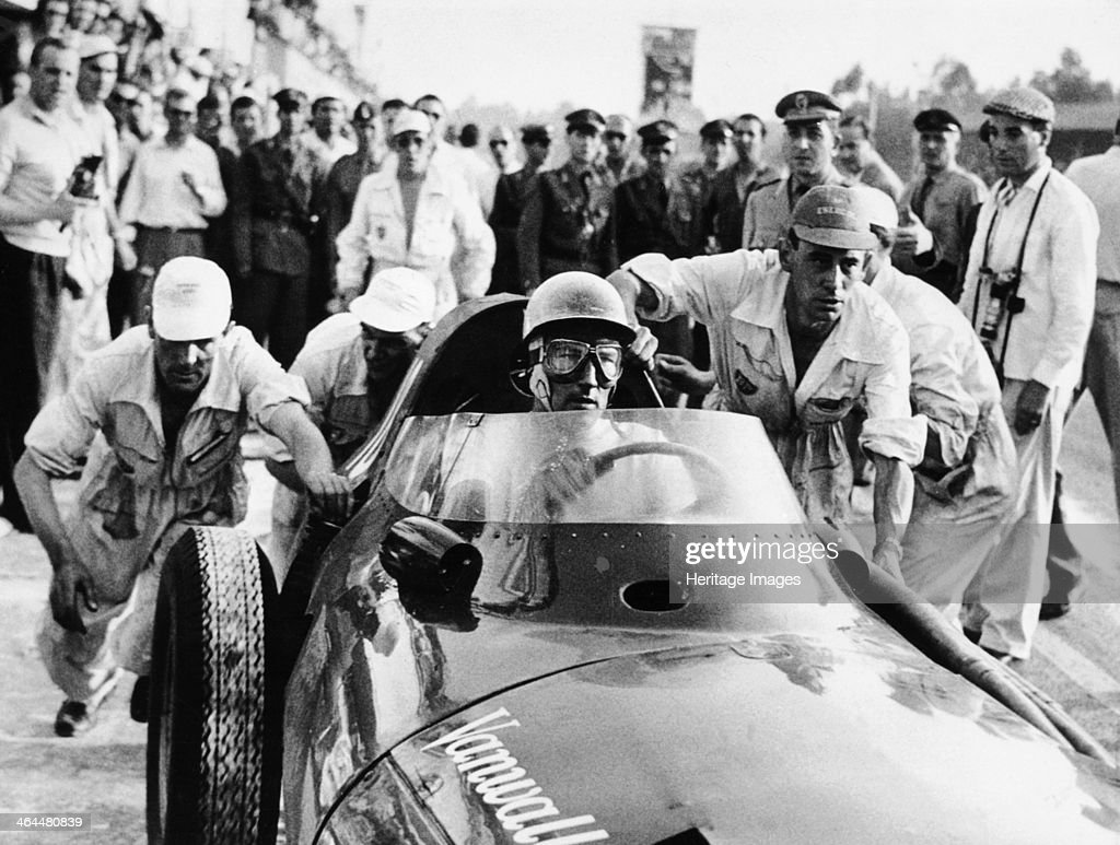 Stirling Moss in a Vanwall, Italian Grand Prix, Monza, 1957. With members of the Vanwall crew behind him. Moss went on to win this race. He was team leader and beat the Maserati and Ferrari teams. Moss began his career in 1947 driving a BMW 328. In 1955 he won his first Grand Prix at Aintree driving a Mercedes, and in 1956 went on to win the Monaco and Italian Grands Prix driving for the Maserati team. He drove Coopers and Lotuses through to 1961, and retired after an accident at Goodwood in 1962.
