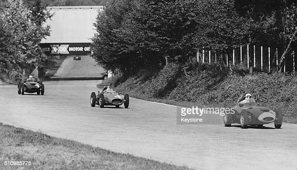 Stirling Moss in a Vanwall VW leading Mike Hawthorn and Stuart LewisEvans in a Vanwall VW during the Italian Grand Prix at the Autodromo Nazionale...