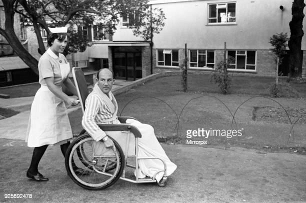 Stirling Moss pictured in a wheelchair being pushed by a nurse in the grounds of the Atkinson Morleys Hospital at Wimbledon Stirling received head...