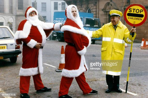 Stirling's slimming Santa's Robert Grant and Peter Hawkins get a helping hand to cross the road from crossing patrol man Douglas Moyer 24th October...
