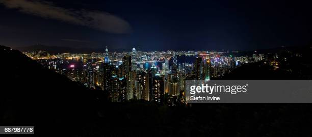 A stitched panorama of Hong Kong's famous skyline and Victoria Harbour taken at night from The Peak showing Central in the foreground and the Kowloon...
