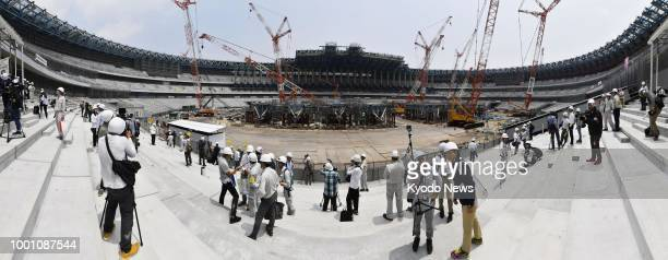 Stitched panoramic photo shows members of the press participating in a tour of Japan's new National Stadium the main venue of the 2020 Tokyo Olympics...