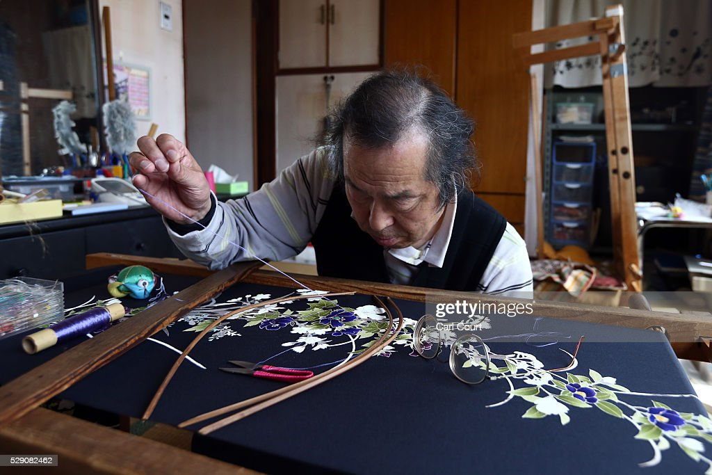 Stitching master Hitoshi Nakano works on a kimono during a stage of its production process at the Sensyo Ichikawa kimono workshop on April 26, 2016 in Kyoto, Japan. The workshop employs a traditional method of dyeing called Kyo-Yuzen. Unique to Kyoto it is used to dye silk fabric for kimonos by hand-painting with natural dyes made from flower petals. The technique can be divided into 26 processes and each part is handled by the master of that process.