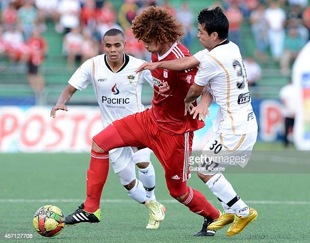 Stiven Tapiero of America de Cali struggles for the ball with Enrique Soto of Llaneros FC during a match between America de Cali and Llaneros FC as...
