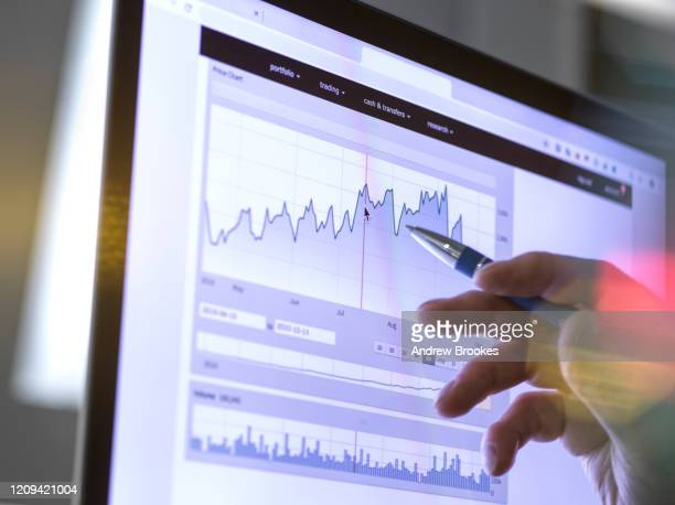 stock broker analyzing the performance of a company stock on the internet. - achievement stock pictures, royalty-free photos & images