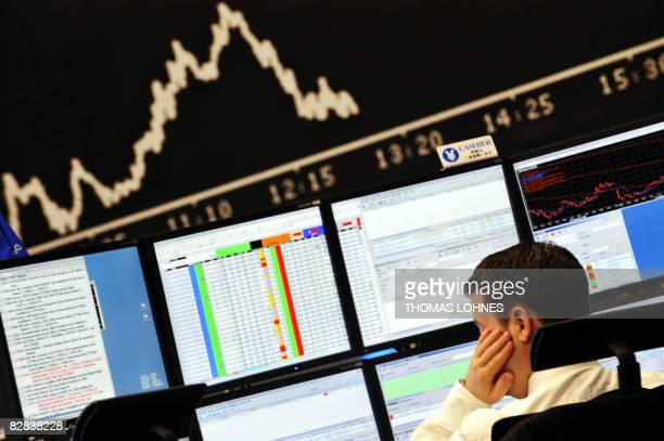 A stock broker looks at his screens at Frankfurt's stock exchange on September 16 as the blue chip DAX 30 was down over three percent at 1300 GMT...