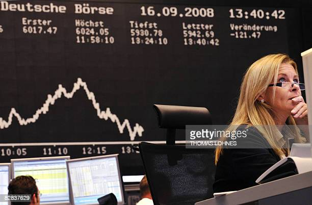 Stock brokers look at their screens at Frankfurt's stock exchange on September 16 as the blue chip DAX 30 was down over three percent at 1300 GMT,...