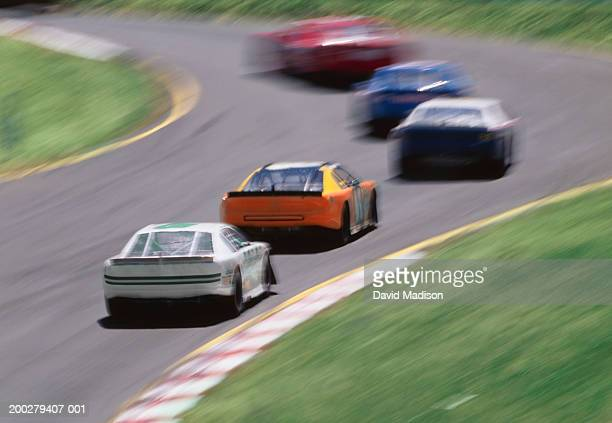 stock car race, elevated view (blurred motion) - nascar stock pictures, royalty-free photos & images