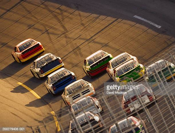 stock car race, safety fence in foreground, elevated view - nascar stock pictures, royalty-free photos & images