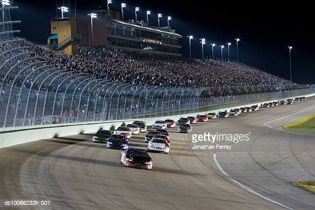 Stock cars racing around track at night (blurred motion)
