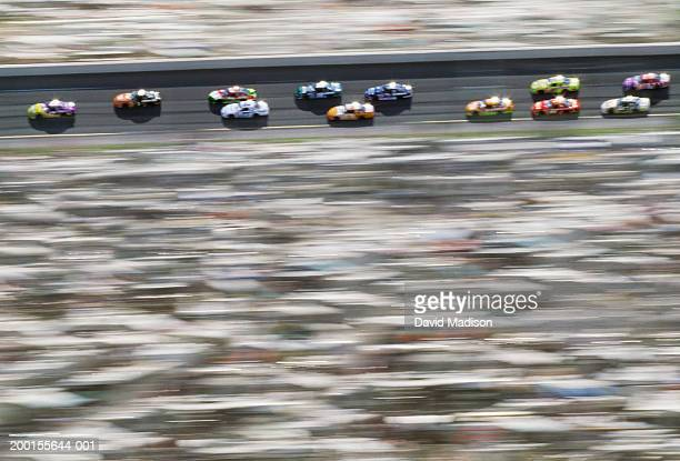 stock cars racing around track (blurred motion, digital enhancement) - nascar stock pictures, royalty-free photos & images