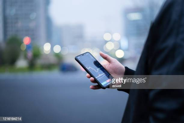 stock chart on smart phone - wuhan stock pictures, royalty-free photos & images