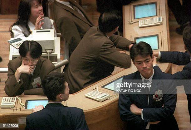 Stock dealers stand idol during a lull in trading at the morning session at the Tokyo Stock Exchange 30 March 1994 The trading session ended with...