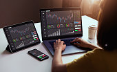 Stock exchange market concept, businesswoman trader looking on laptop and tablet, smartphone with graphs analysis candle line in office room, diagrams on screen.