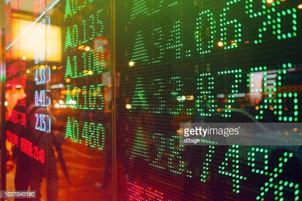 stock exchange market display screen board on the street showing stock rises in green colour - financiën en economie stockfoto's en -beelden