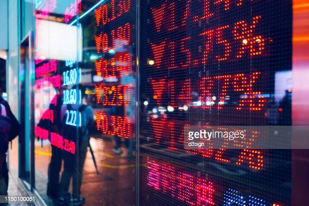 stock exchange market display screen board on the street showing stock market crash sell-off in red colour - börse stock-fotos und bilder