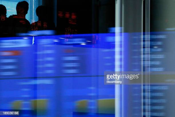 Stock figures are reflected on a glass window against the silhouettes of visitors at the Tokyo Stock Exchange in Tokyo Japan on Thursday Oct 17 2013...