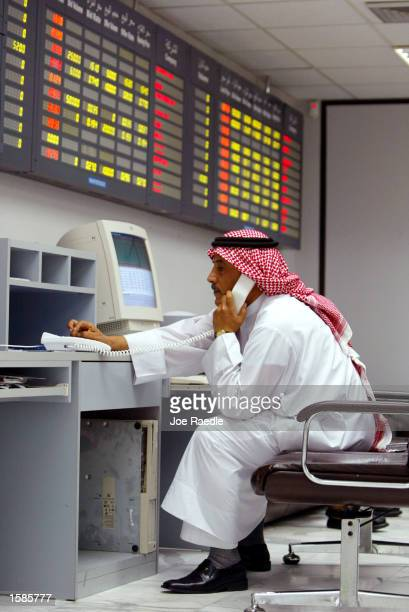Stock investor Abdul Roof Arsisi works the on the phone as he conducts business in the stock exchange room November 4 2002 in Manama Bahrain With a...