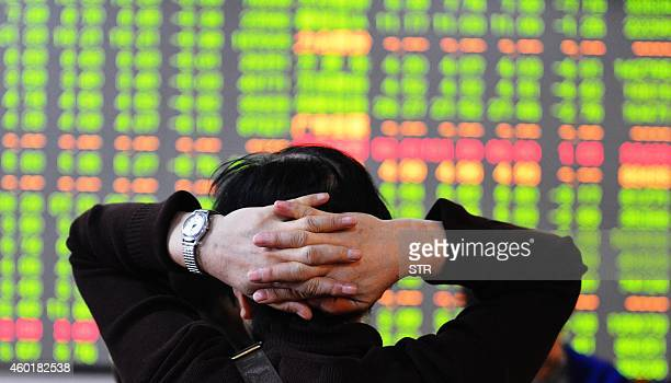 A stock investor checks the share prices at a security firm in Hangzhou east China's Zhejiang province on December 9 2014 Shanghai shares plunged...