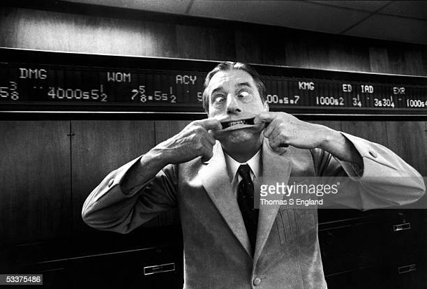 Stock market analyst Joseph Granville making a funny face in front of an electronic stock ticker