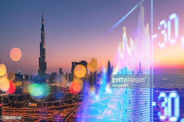 stock market exchange on a skyscraper in dubai background - gulf countries stock pictures, royalty-free photos & images