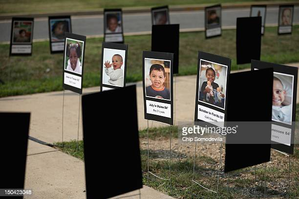 Stock photographs representing children who have died after being left unattended in vehicles are on display during a news conference to launch the...