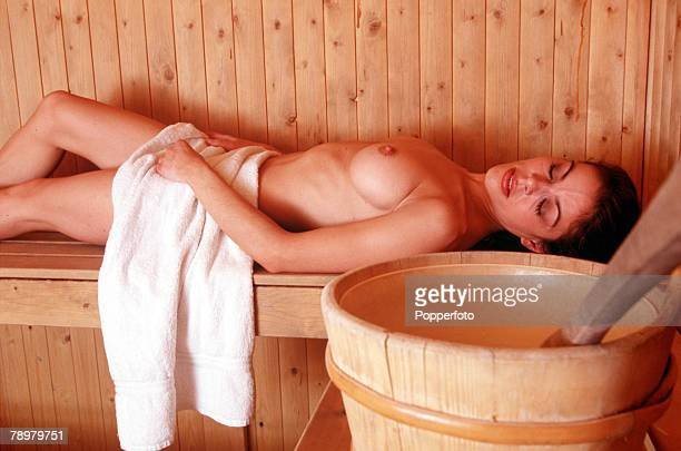 Stock Photography A nude woman lying inside a sauna as she relaxes in the heat on a bench with a towel over her waist