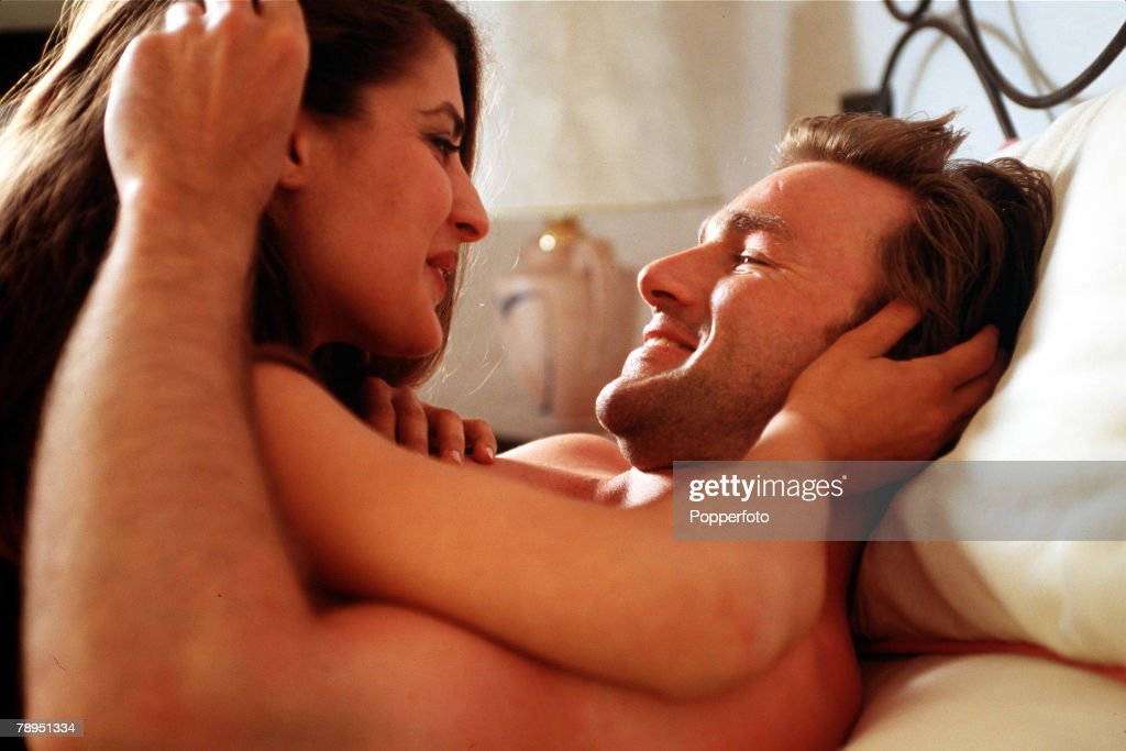 Stock Photography, A portrait of a man and woman making love in bed, The woman who is on lying on top of the man is smiling whilst looking into his eyes, and they are embraced within each others arms