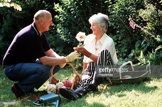 A portrait of a mature couple aged 5060 years old both smiling whilst the man presents the lady with a flower from a basket in a sunlit garden