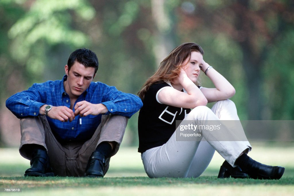 Stock Photography. A young couple in casual dress sitting in the park, the woman appears upset and has back turned on the man. : News Photo
