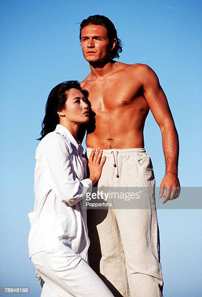 Stock Photography Bare chested well toned man standing high against a deep blue sky with a glamourous young woman at his side