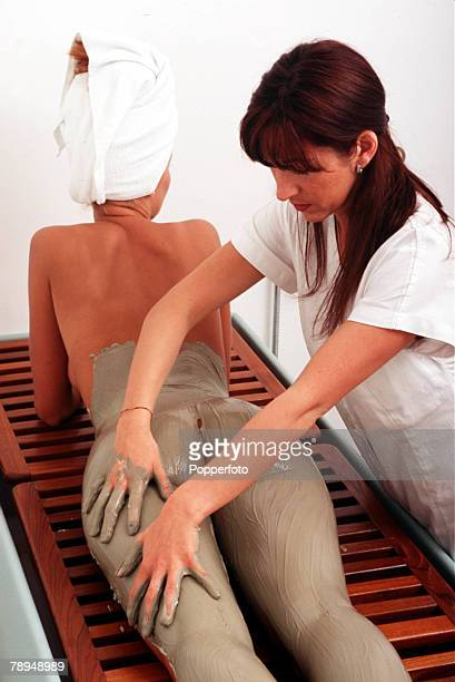 Stock Photography Beauty therapist applies a mud pack to the lower back buttocks and legs of a woman who is lying on a bench and wearing a towel...